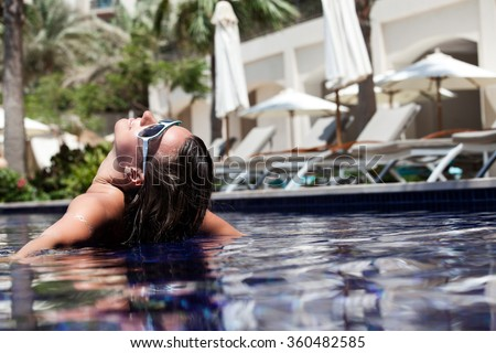 Young attractive woman in in pool with head thrown back side view. Swimming Pool, Health Spa, Relaxation. Summer luxury vacation.