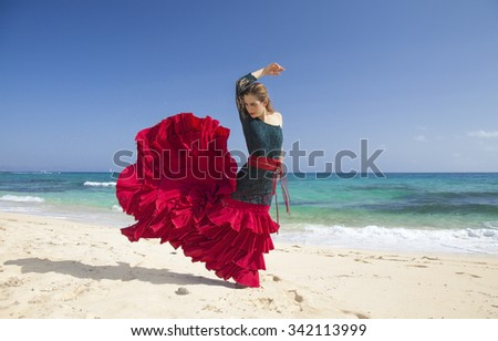 young attractive woman in red and green  flamenco dress by ocean shore - stock photo