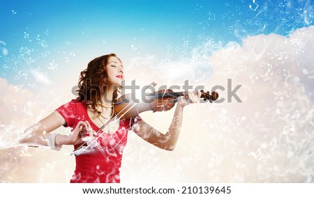 Young attractive woman in red dress playing violin - stock photo
