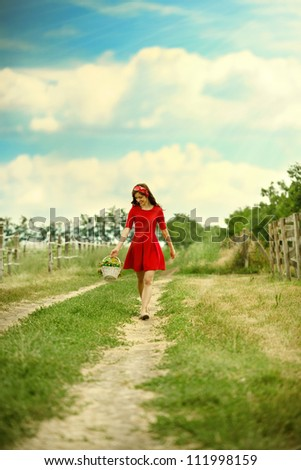 Young attractive woman in red dress  walking in nature