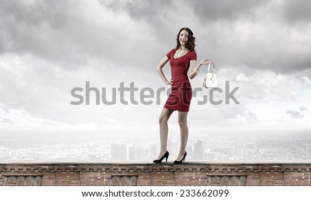 Young attractive woman in red dress with bag in hand