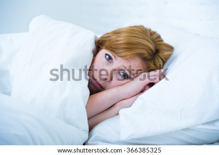 young attractive woman in sad and depressed face expression with eyes wide open lying in bed looking sick and unable to sleep suffering depression , nightmares or insomnia sleeping disorder - stock photo
