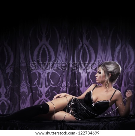 Young attractive woman in sexy lingerie posing in luxury interior - stock photo