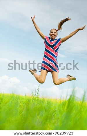 young, attractive woman in striped dress jumps up against the blue sky with clouds and green fields