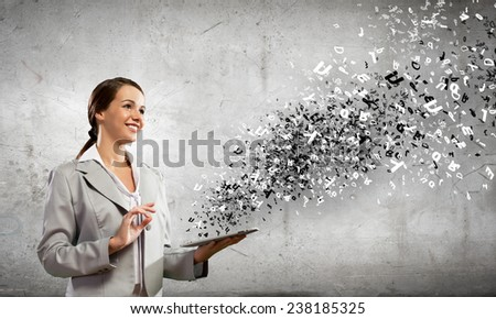 Young attractive woman in suit with tablet pc in hands - stock photo