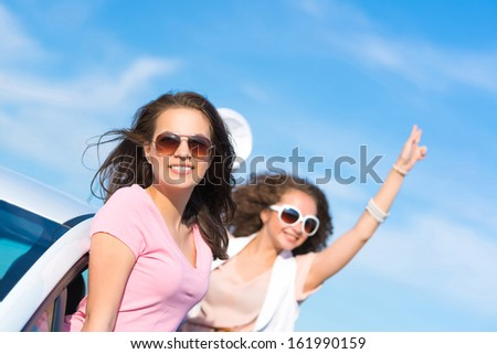 young attractive woman in sunglasses got out of the car window and laugh