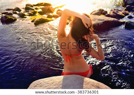 Young attractive woman in swimsuit standing in water  - stock photo