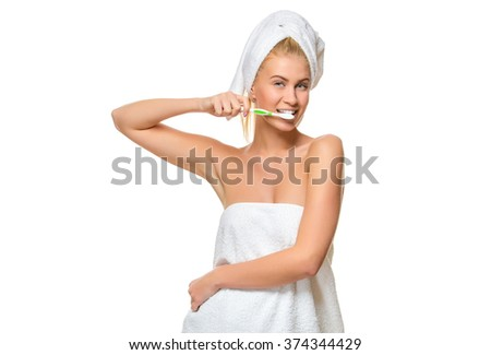 Young attractive woman in towel brushing her teeth with toothbrush  - stock photo