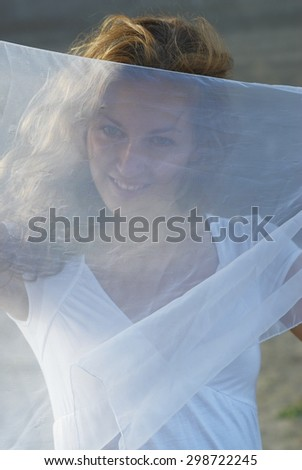 Young attractive woman in white dress and holding white scarf on beach - stock photo