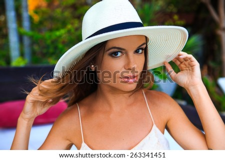 Young attractive woman in white hat posing near the tropical swimming pool