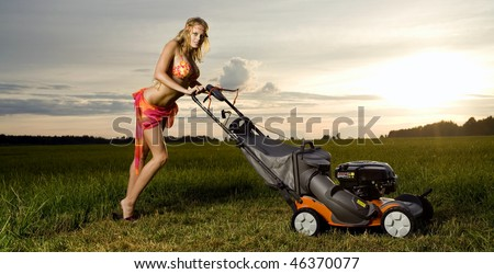 Young attractive woman is mowing the grass . - stock photo