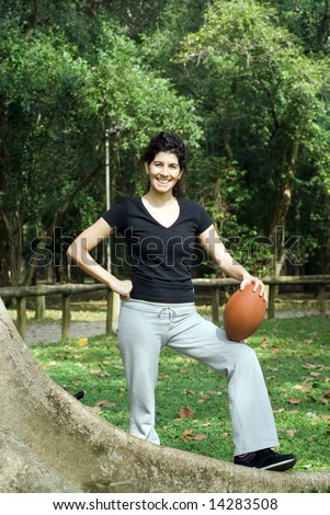 Young, attractive woman is posing next to a tree.  She is smiling and holding a football.   Vertically framed shot - stock photo