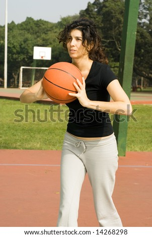 Young, attractive woman is standing on an outdoor basketball court.  She is holding a basketball and looking as if she is about to pass it to someone else.  Vertically framed shot. - stock photo