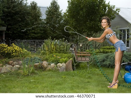 Young attractive woman is watering a garden. - stock photo