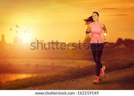 Young attractive woman jogging outdoor on sunset - stock photo
