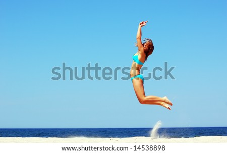 Young attractive woman jump on the beach
