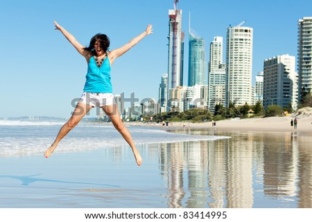 young attractive woman jumps with joy on the beach with modern city in background (gold coast,queensland,australia) - stock photo