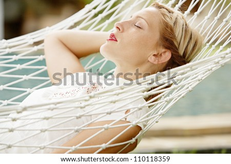 Young attractive woman laying and relaxing on a white hammock in a tropical garden near a swimming pool. - stock photo