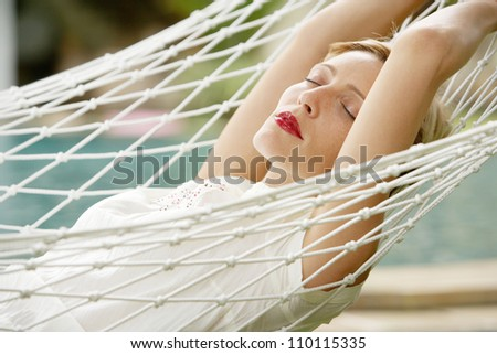 Young attractive woman laying down on a white hammock in a garden, while on vacations. - stock photo