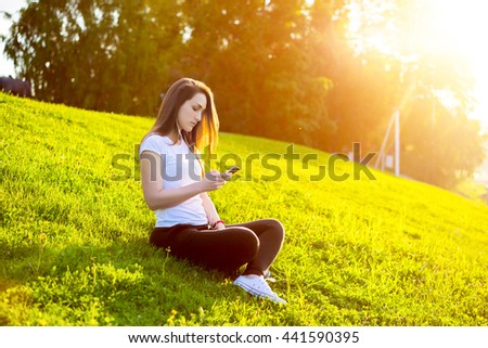 Young attractive woman listen to music with a smart phone in the city park. Blurred background with copy space area for a text. - stock photo