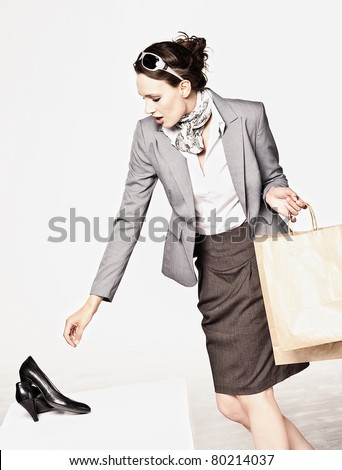 Young attractive woman looking at a pair of shoes at a shoe store - stock photo