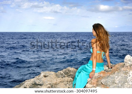 young attractive woman looking at ocean horizon sitting thoughtful on rock cliff by sea shore in glamour dress under summer blue sky in relax and vacation concept - stock photo