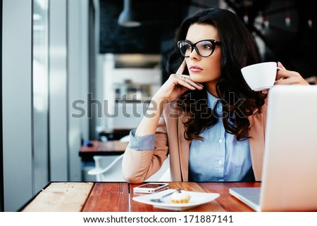 Young attractive woman looking away thoughtfully - stock photo