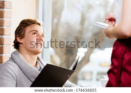 Young attractive woman making order at restaurant - stock photo