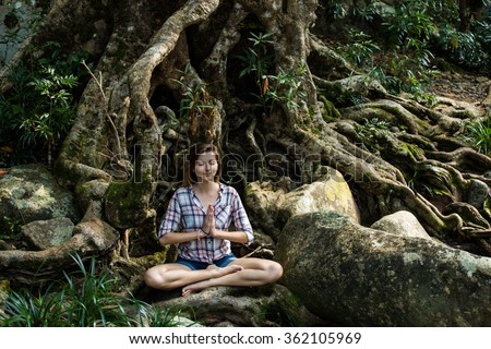 Young attractive woman meditate under big banyan tree in asia, yoga lifestyle concept - stock photo
