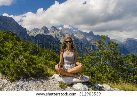 Young attractive woman meditating in the mountains