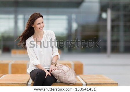 Young attractive woman model sitting on a wooden bench waiting for someone - stock photo