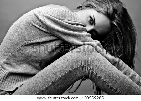 Young attractive woman on casual clothes siting on studio floor. Black-white photo. - stock photo