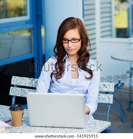Young attractive woman outside working at her laptop with her coffee. - stock photo