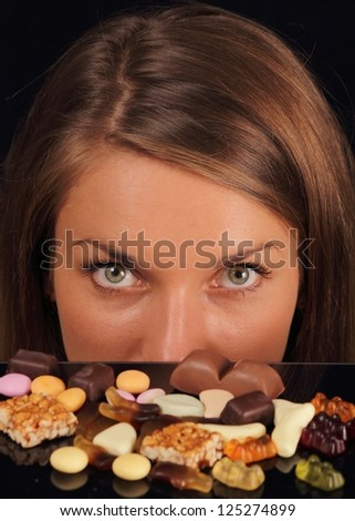 Young attractive woman over sweets looking in camera - stock photo