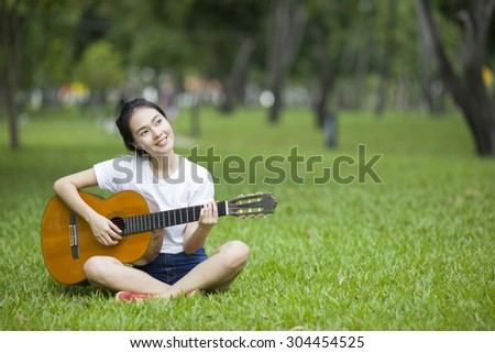 Young attractive woman playing acoustic guitar - stock photo