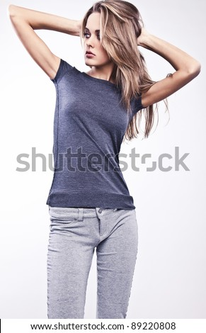 Young attractive woman pose  in casual gray clothing. - stock photo