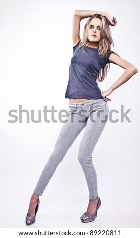Young attractive woman pose  in casual gray clothing.