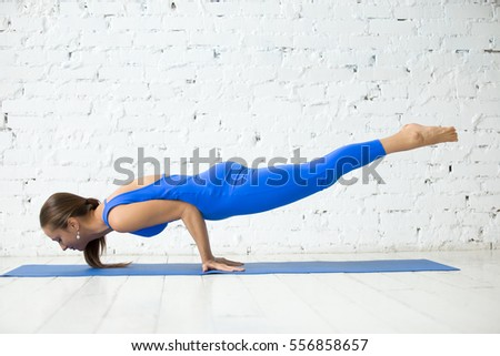 Young attractive woman practicing yoga, standing in Peacock exercise, Mayurasana pose, working out, wearing sportswear, blue suit, indoor full length, white loft studio background
