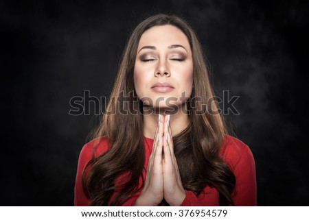 Young attractive woman praying over dark background. - stock photo