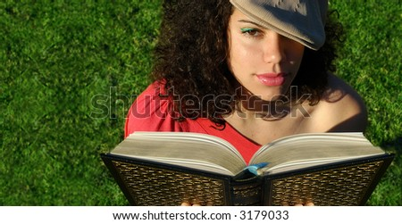 Young attractive woman reading a book as the sun sets.  Banner is usable as copy space or can be cropped down for a tighter shot. - stock photo
