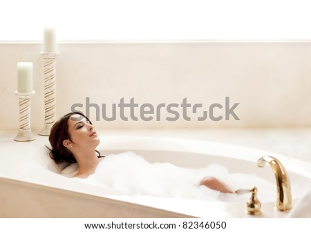 Young attractive woman relaxing in a bubble bath - stock photo