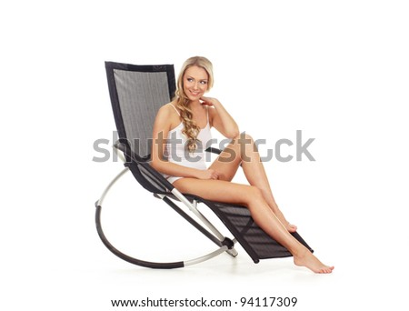 Young attractive woman relaxing in the modern armchair - stock photo