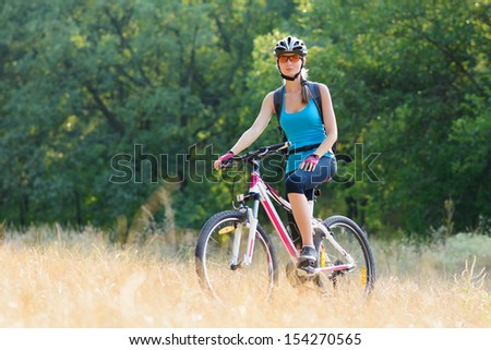 Young Attractive Woman Riding the Bike on the Beautiful Meadow in the Forest - stock photo