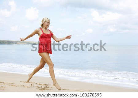 Young attractive woman running on a golden sand beach, feeling happy. - stock photo
