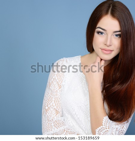 Young attractive woman's portrait, beautiful girl with long hair and white dress, over blue studio shot - stock photo
