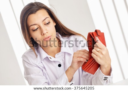 Young attractive woman searching money in the wallet. - stock photo