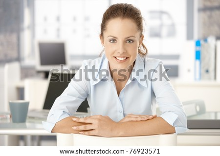Young attractive woman sitting at desk in office, smiling.? - stock photo