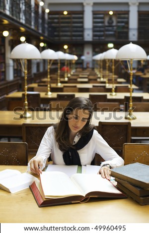 Young attractive woman sitting at desk in old university library studying books, front view. - stock photo