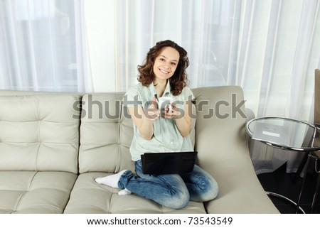 Young attractive woman sitting in a sofa with a cup of coffee and a laptop