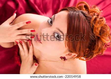 young attractive woman sitting in long red dress on red background. view from above. - stock photo
